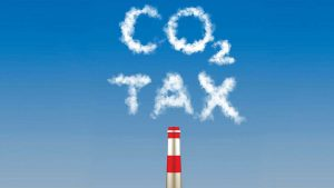 Carbon tax written in emissions smoke from a factory stack